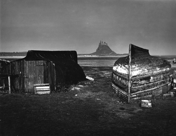 Picture of Sheds made from upturned boats with Lindisfarne Castle in the background, Lindisfarne (Holy Island), Northumberland