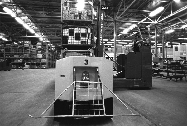 Picture of A worker operating a Lansing Bagnall forklift truck in a warehouse with mechanized storage systems