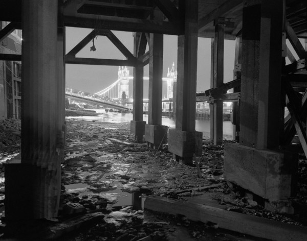 Picture of Sugar Dock foreshore, London: looking through the concrete piers towards Tower Bridge at night