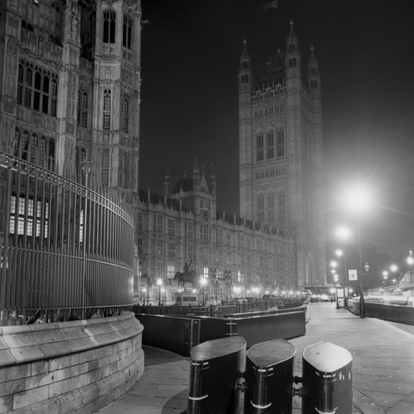 Picture of Houses of Parliament, Westminster, London, with security barriers in the foreground, at night